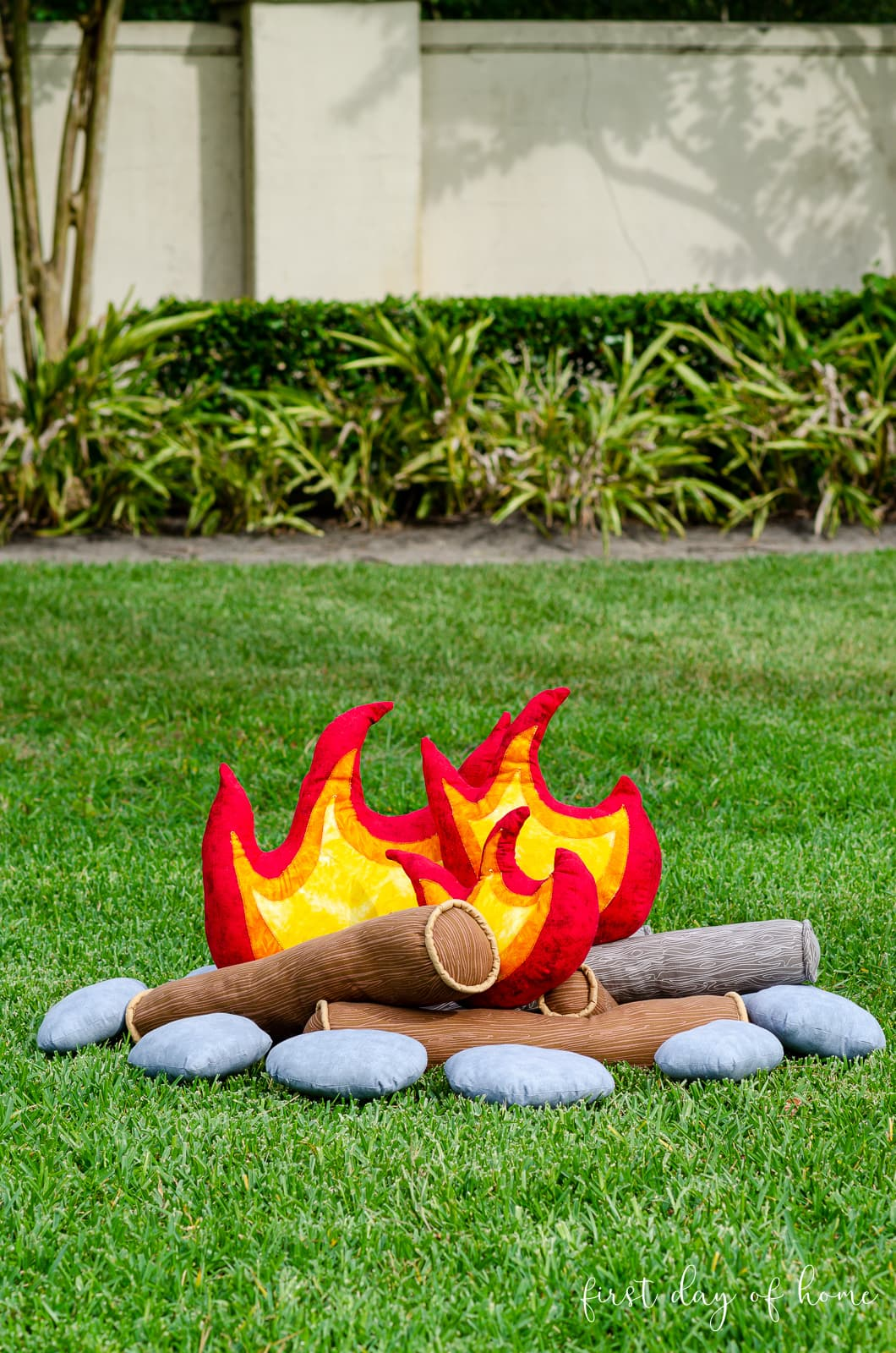 Kids pretend campfire set with flames, logs and stones on outdoor lawn