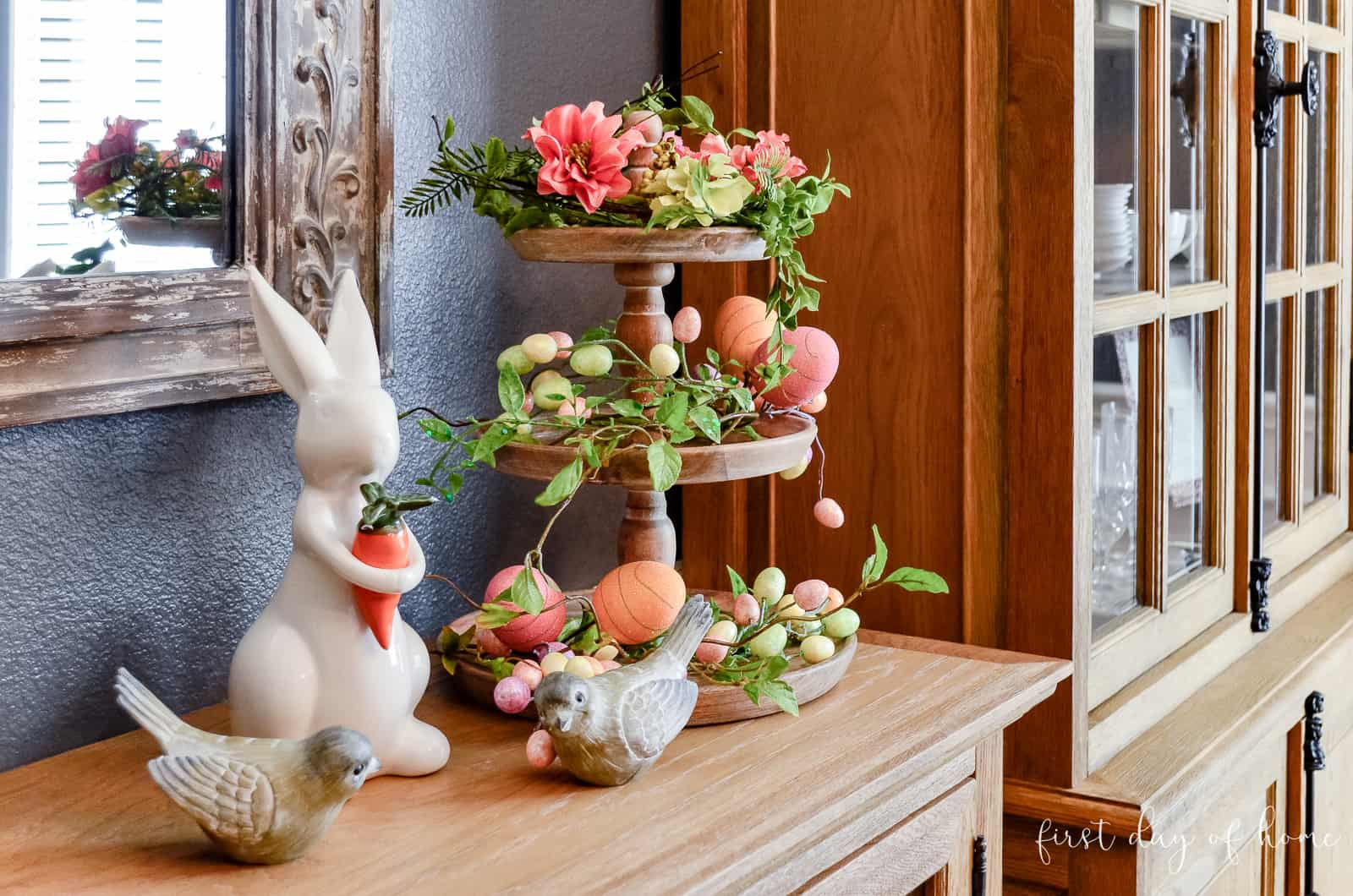 Ceramic bunny holding carrot next to three tiered tray covered with Easter egg decor and greenery