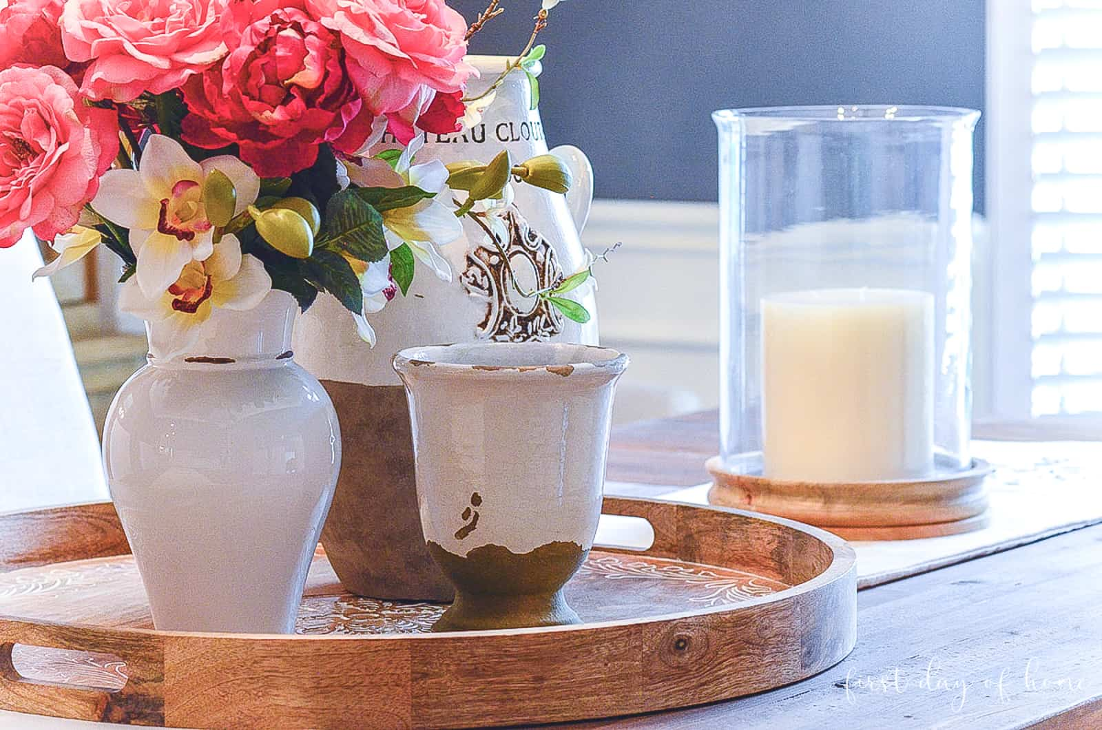 Trio of ceramic pottery on wooden tray in center of dining room table