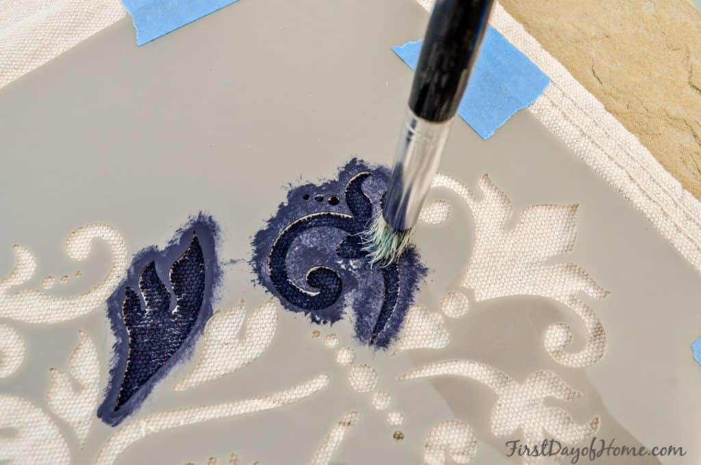 Applying paint to custom stencil on drop cloth