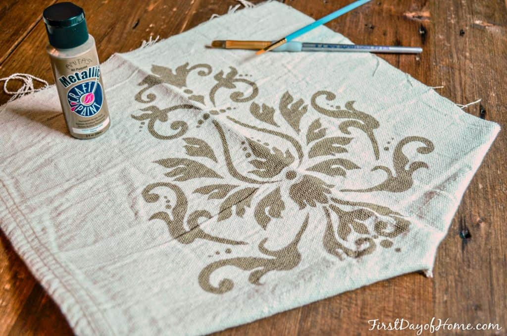 Practicing stenciling a custom table runner using drop cloth and acrylic paints