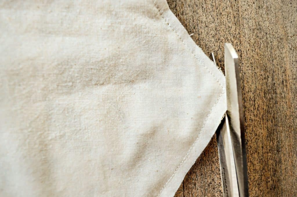Trim pointed edges on ends of a drop cloth table runner to prevent bulk