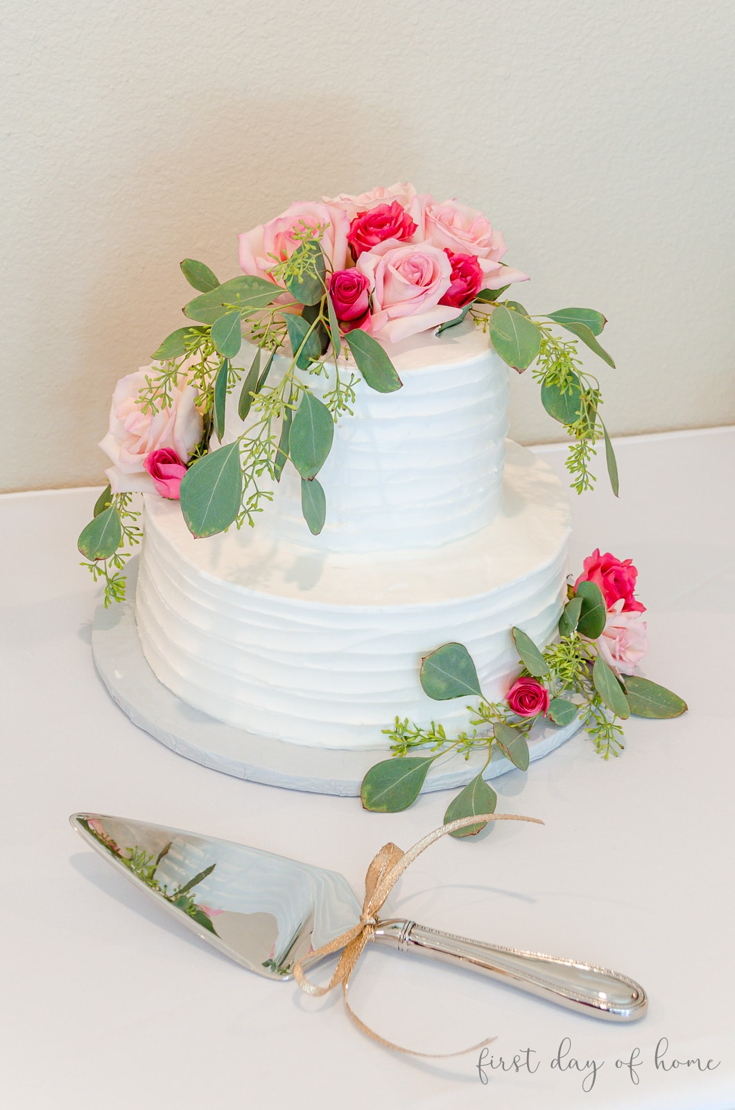 White bridal shower cake with fresh eucalyptus leaves and fresh roses