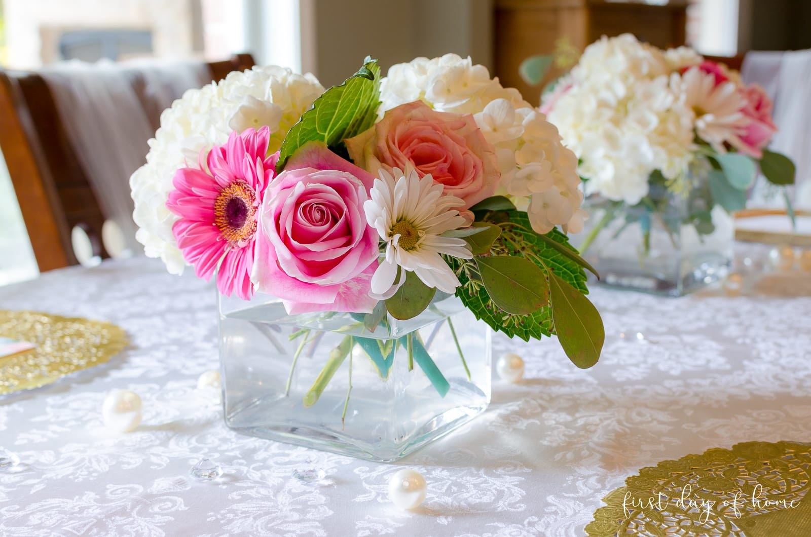 Bridal shower centerpiece floral arrangement in square vase with roses, daisies, hydrangeas and eucalyptus