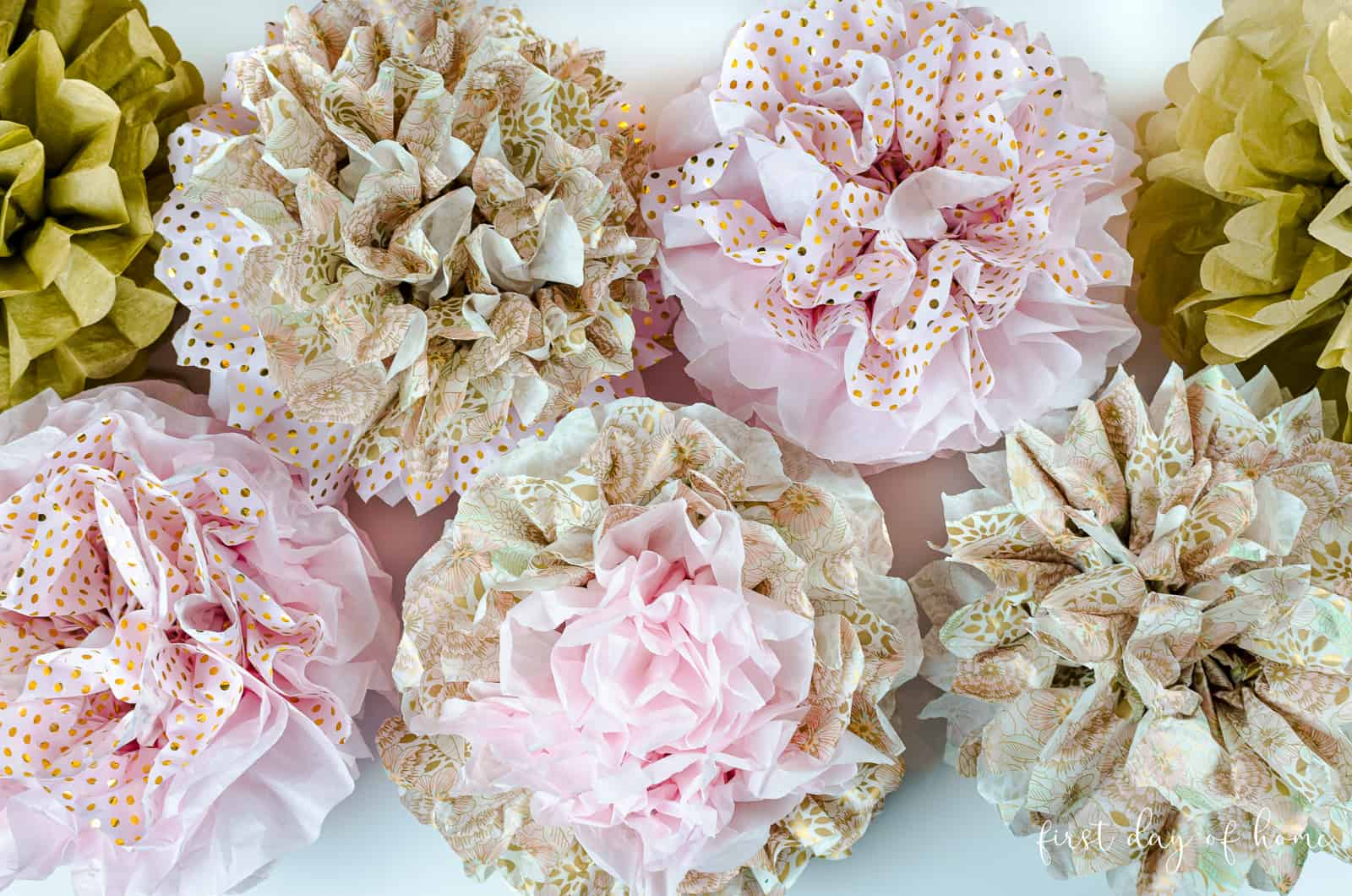 Multicolored tissue paper pom poms in pink and floral patterns