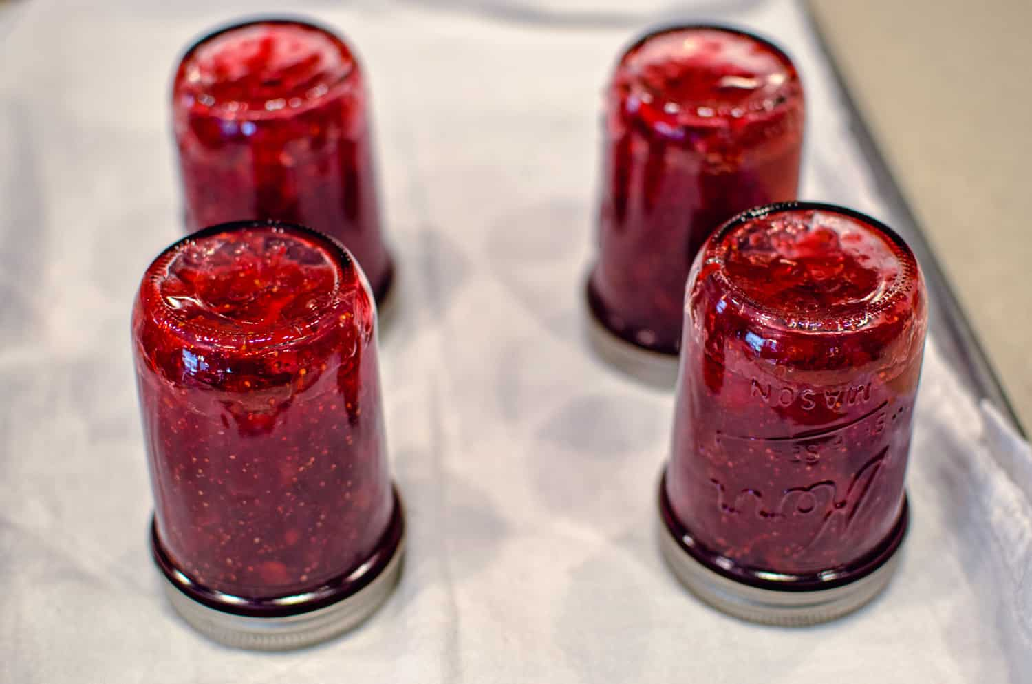 Final step in how to make fig preserves (mason jars turned upside down)