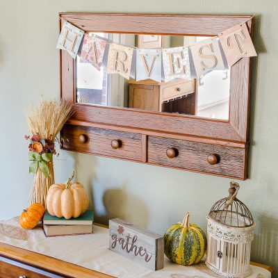 Fall banner spelling HARVEST hanging on farmhouse mirror with wheat, pumpkins and fall decor in breakfast room