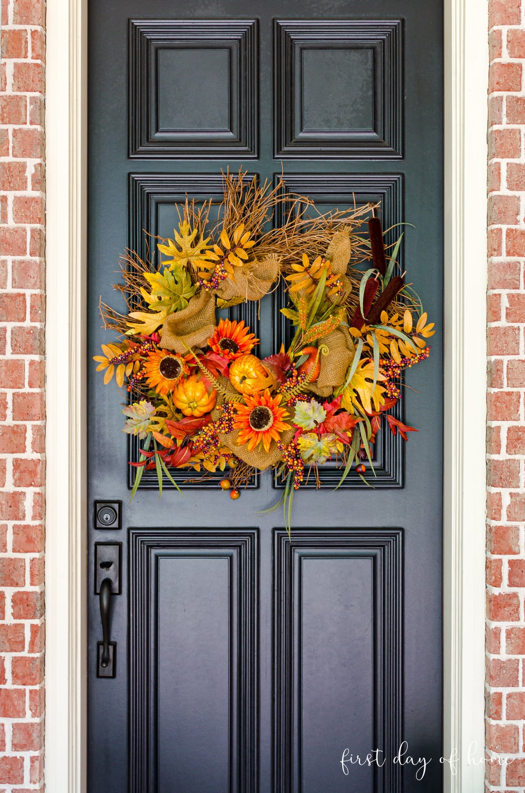 Black front door with fall wreath in orange and yellow