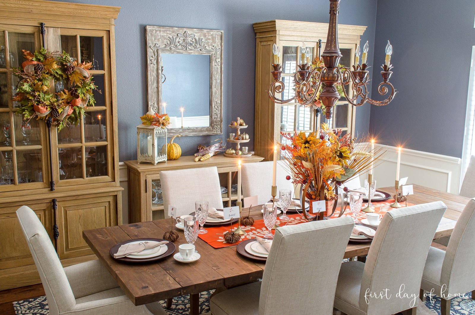 Fall dining room decor with fall wreaths on cabinets and formal tablescape