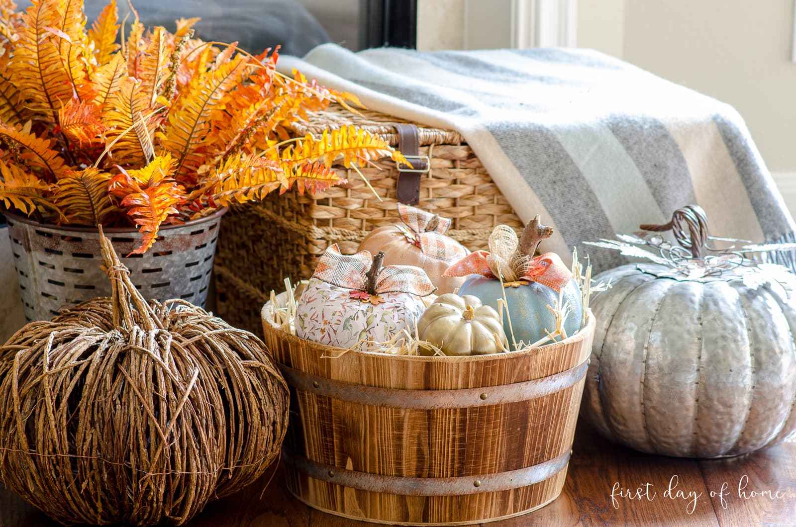 Fall decor by fireplace with bushel basket, woven pumpkins and metal pumpkin decor