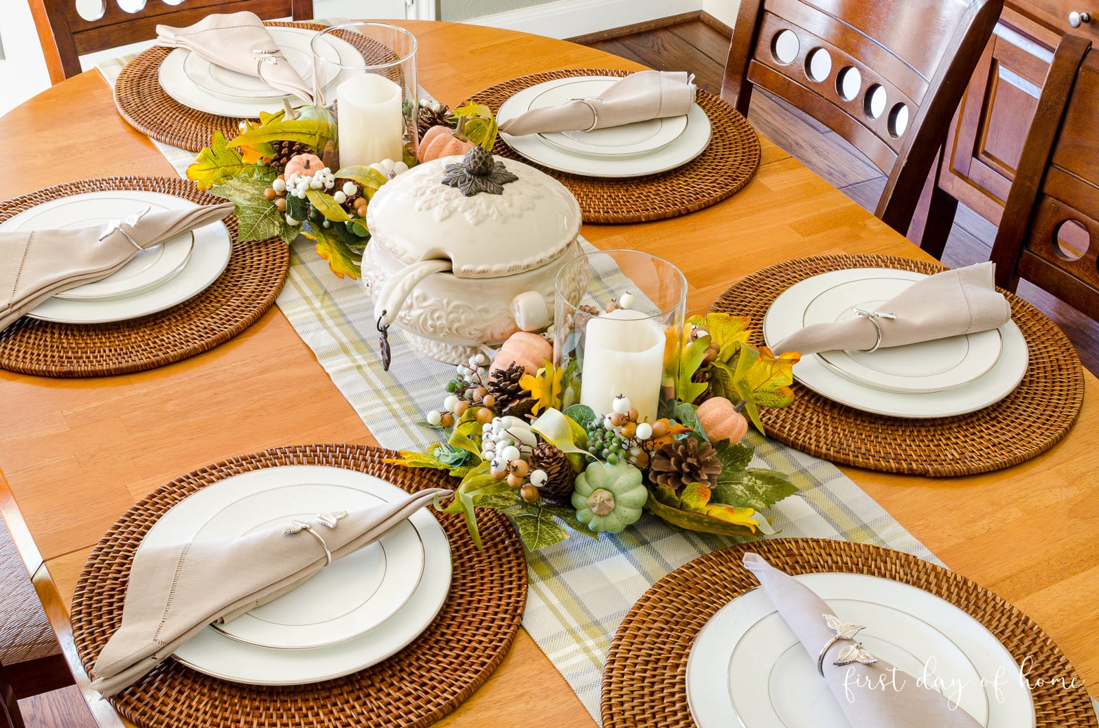 Fall tablescape with woven chargers, neutral linen napkins, soup tureen and hurricane candle holders