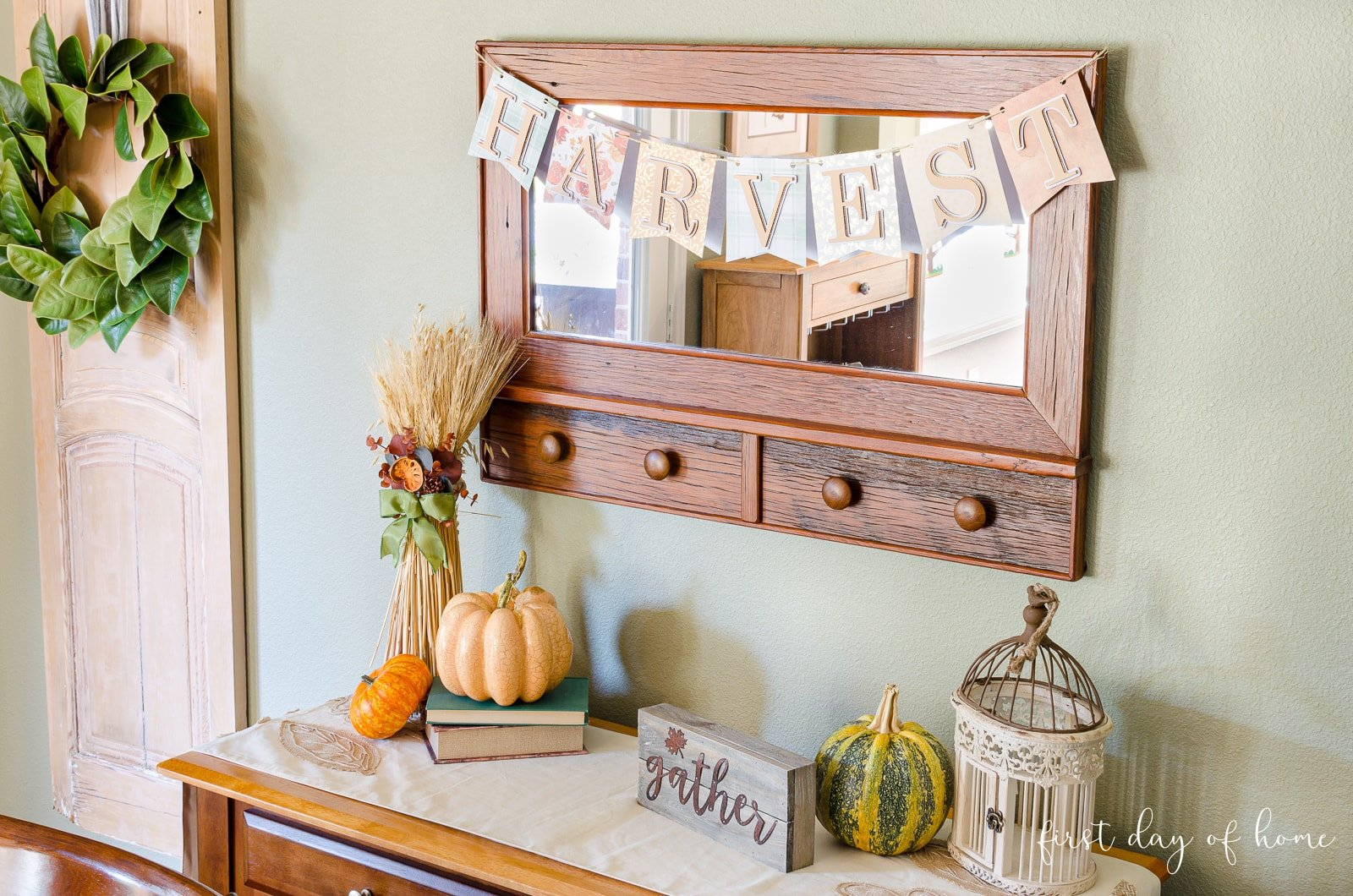 DIY harvest pennant banner on breakfast room mirror above sideboard with fall decor