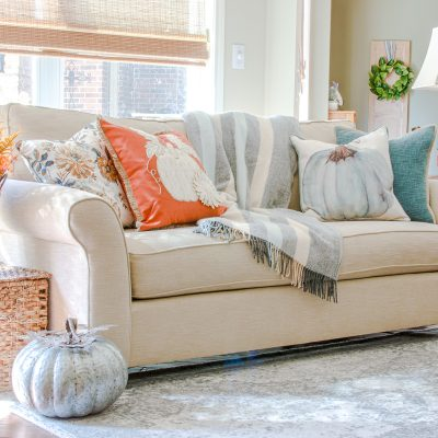 Close up of sofa with aqua and orange fall decor color scheme