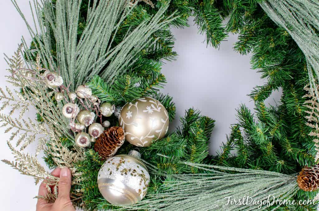 Homemade Christmas wreath with frosted pine needles and matte metallic ornaments