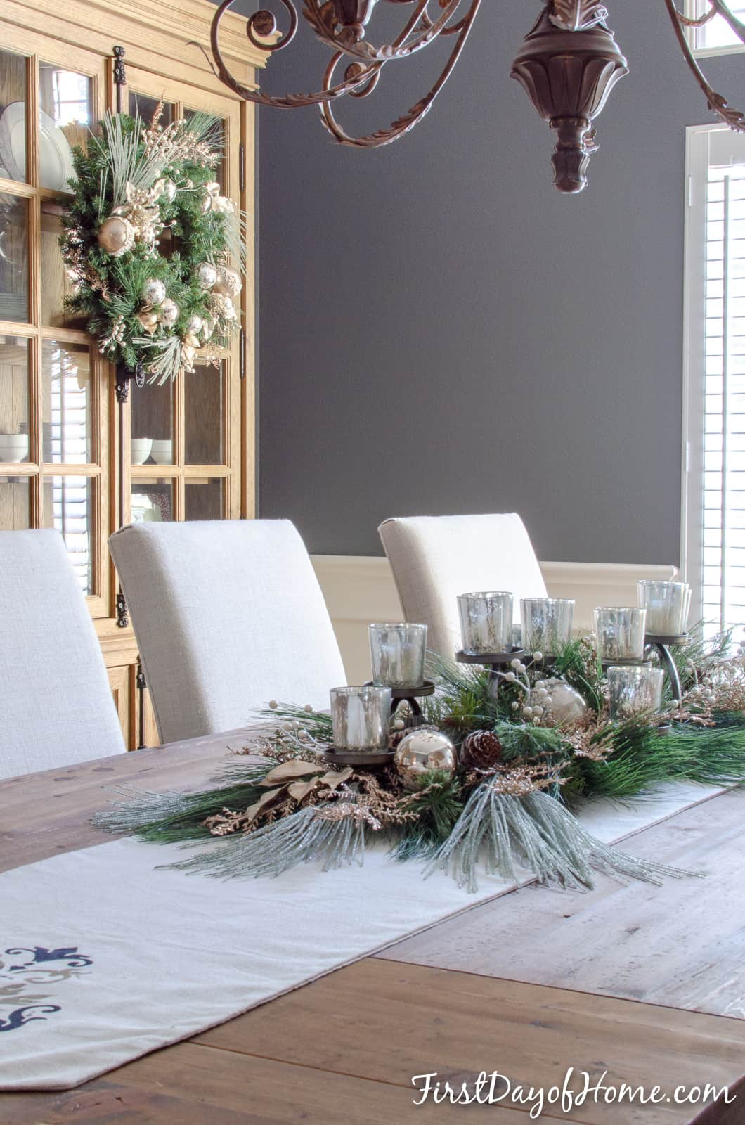 DIY holiday centerpiece with mercury glass candle holders and mixed metallic ornaments and greenery.