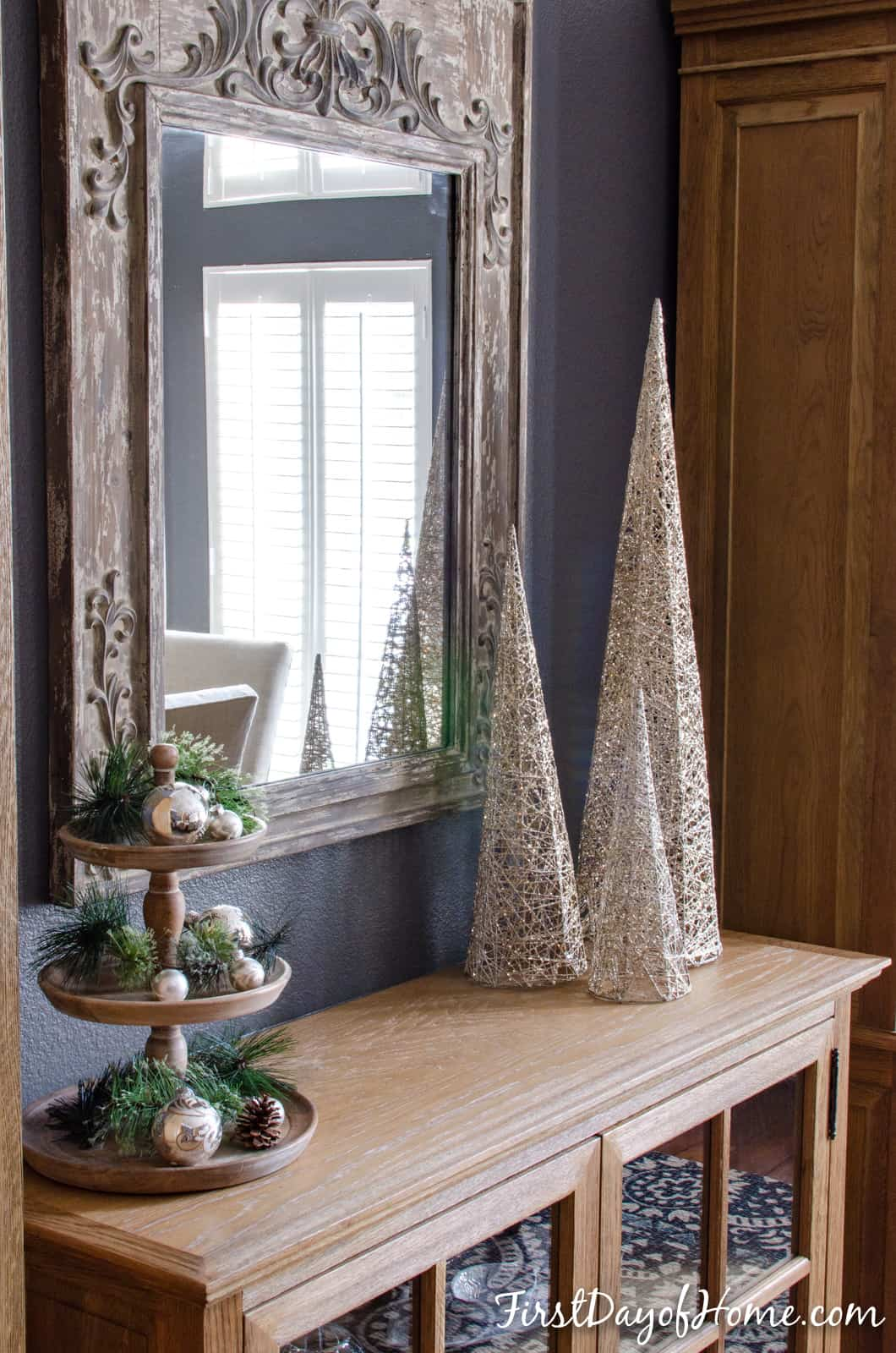 Trio of modern shimmering Christmas trees on buffet sideboard table and 3-tier stand with Christmas decor