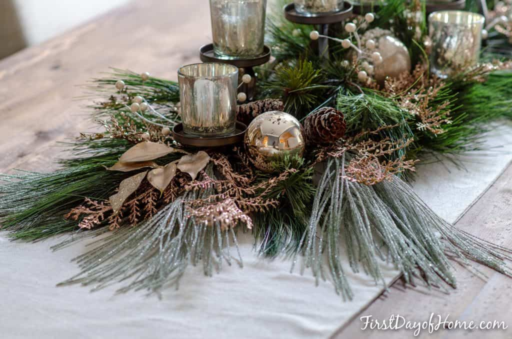 DIY holiday centerpiece with mixed faux greenery, silver and gold ornaments, frosted pine cones and mercury glass votives