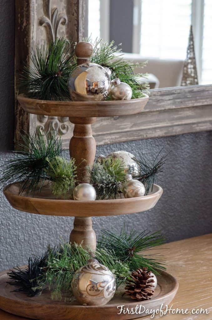 Three tiered tray decorated for Christmas with faux pine greenery and silver ornaments