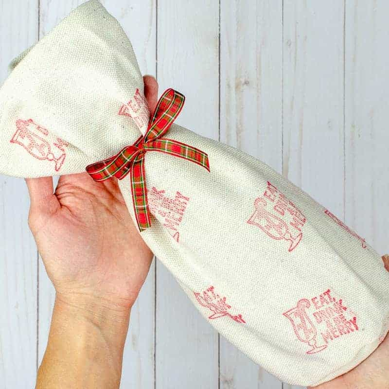 Easy wine bag created using a simple sewing pattern with drop cloth, fabric stamps and dollar ribbon
