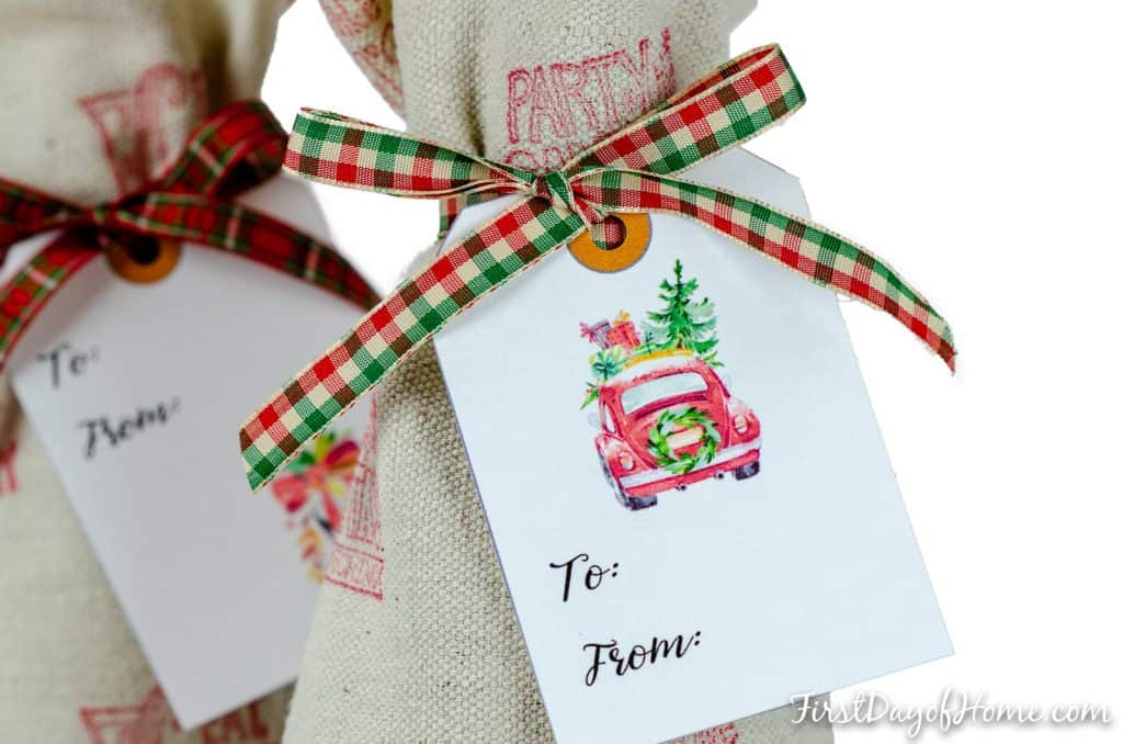 Three DIY wine bottle gift bags made from an easy to sew pattern using drop cloth, stamps and ribbon.