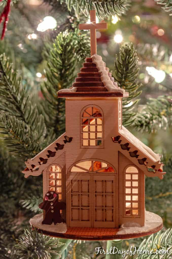 Gingerbread cottage wooden ornament hanging on tree with couple inside