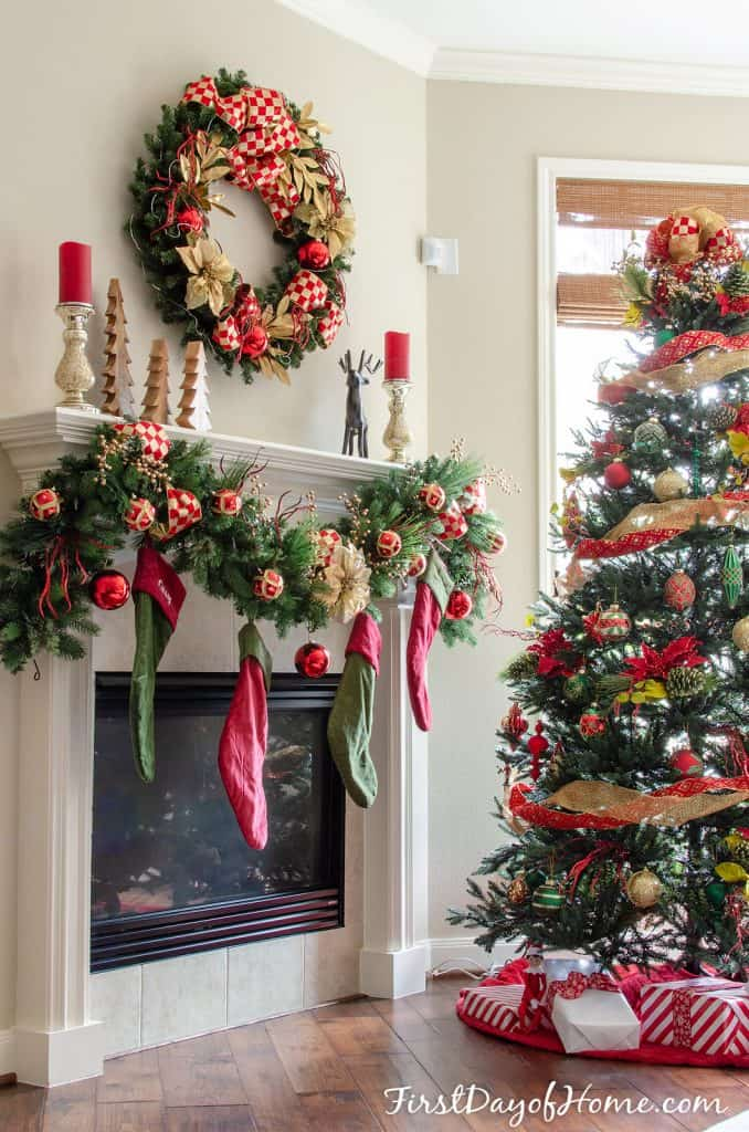 Christmas wreath and mantel by Christmas tree, decorated with red and gold