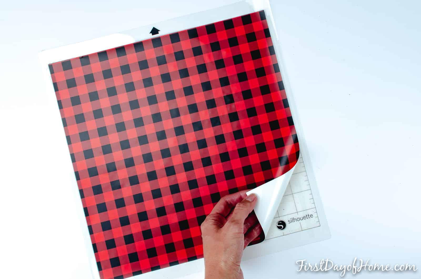 Placing buffalo plaid heat transfer vinyl on Silhouette Cameo cutting mat to make Valentine's Day DIY shirt