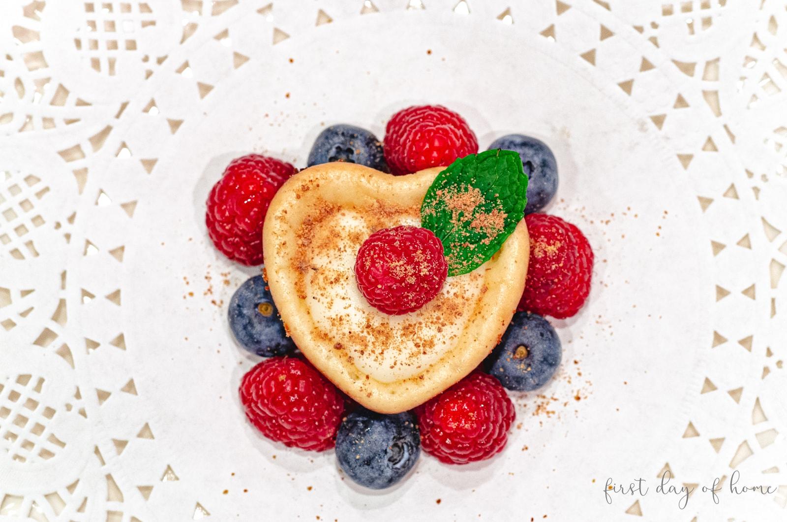 Heart shaped mini cheesecake with raspberries and blueberries
