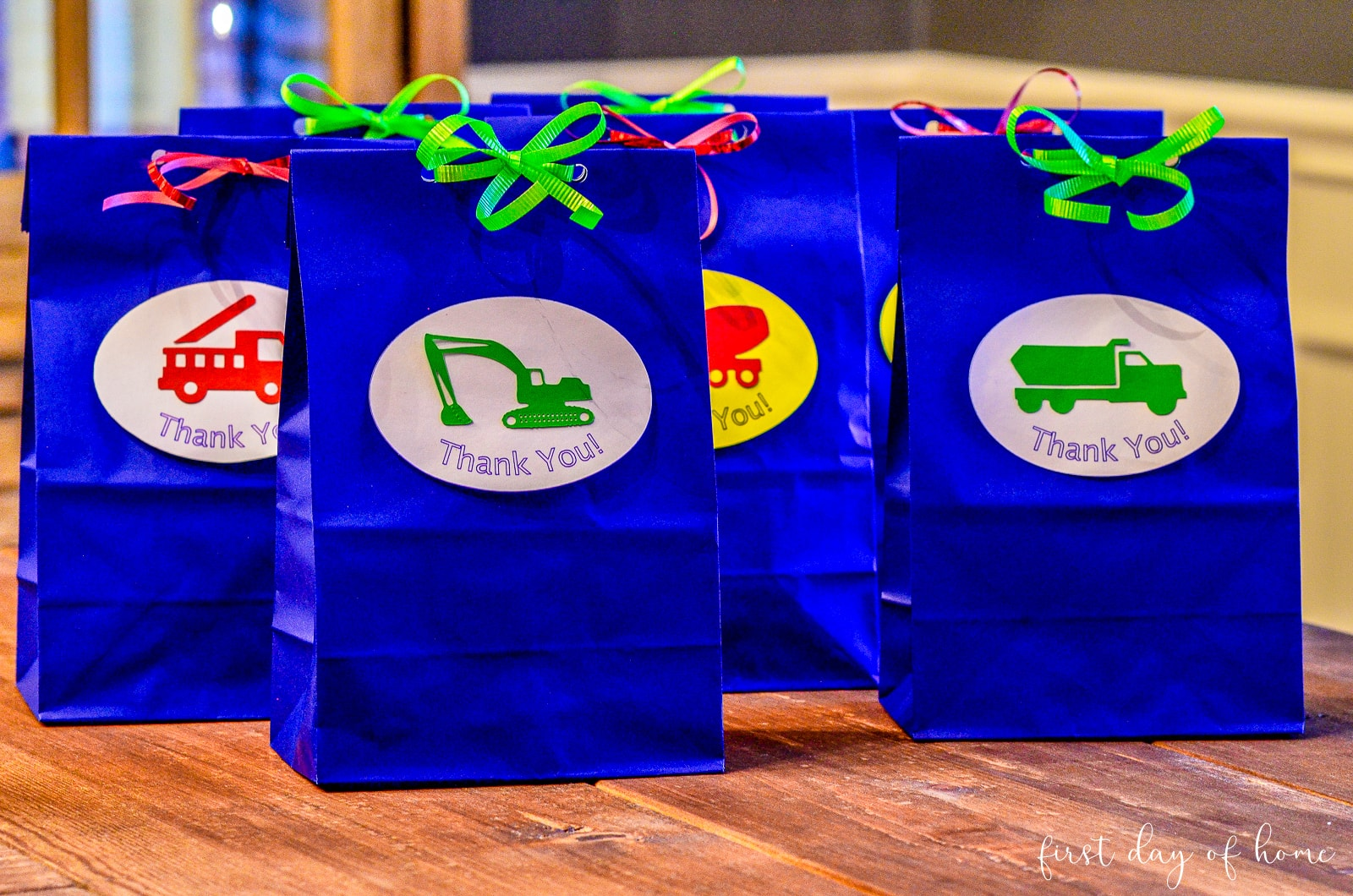 Blue gift bags with vehicles on front, made with Cricut machine for transportation themed birthday party
