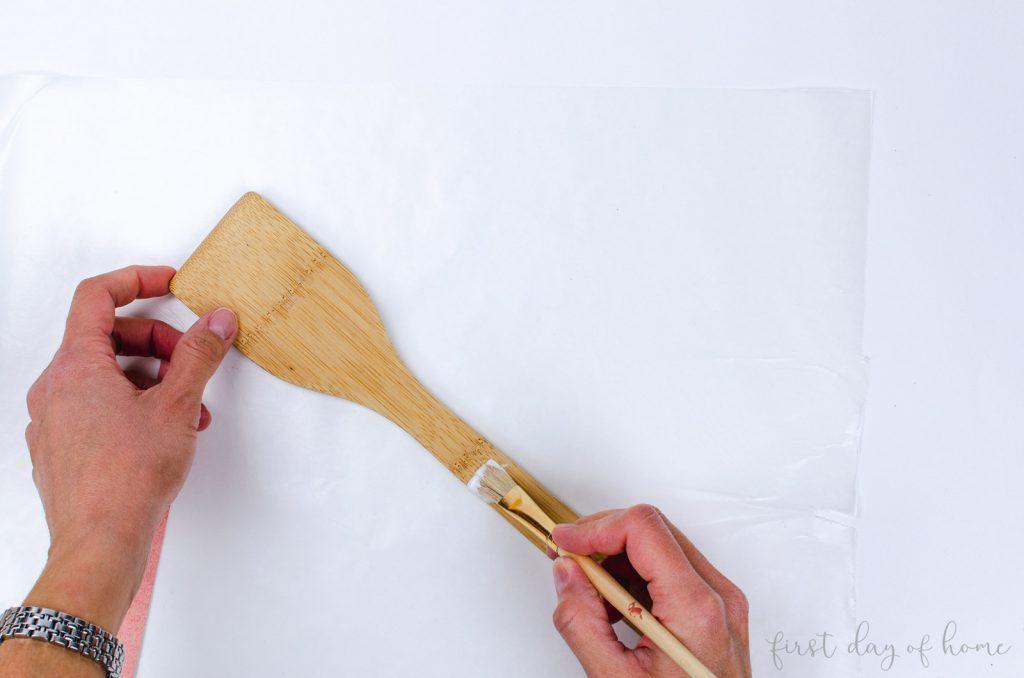 Applying mod podge to make decoupage wooden spoon