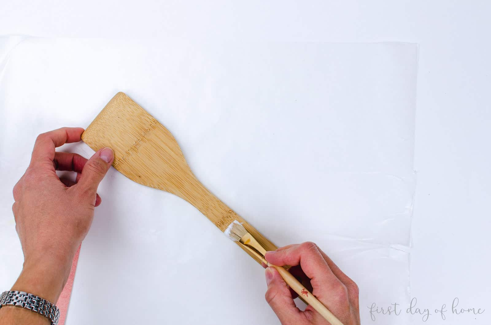 Applying mod podge to make decoupage wooden spoon