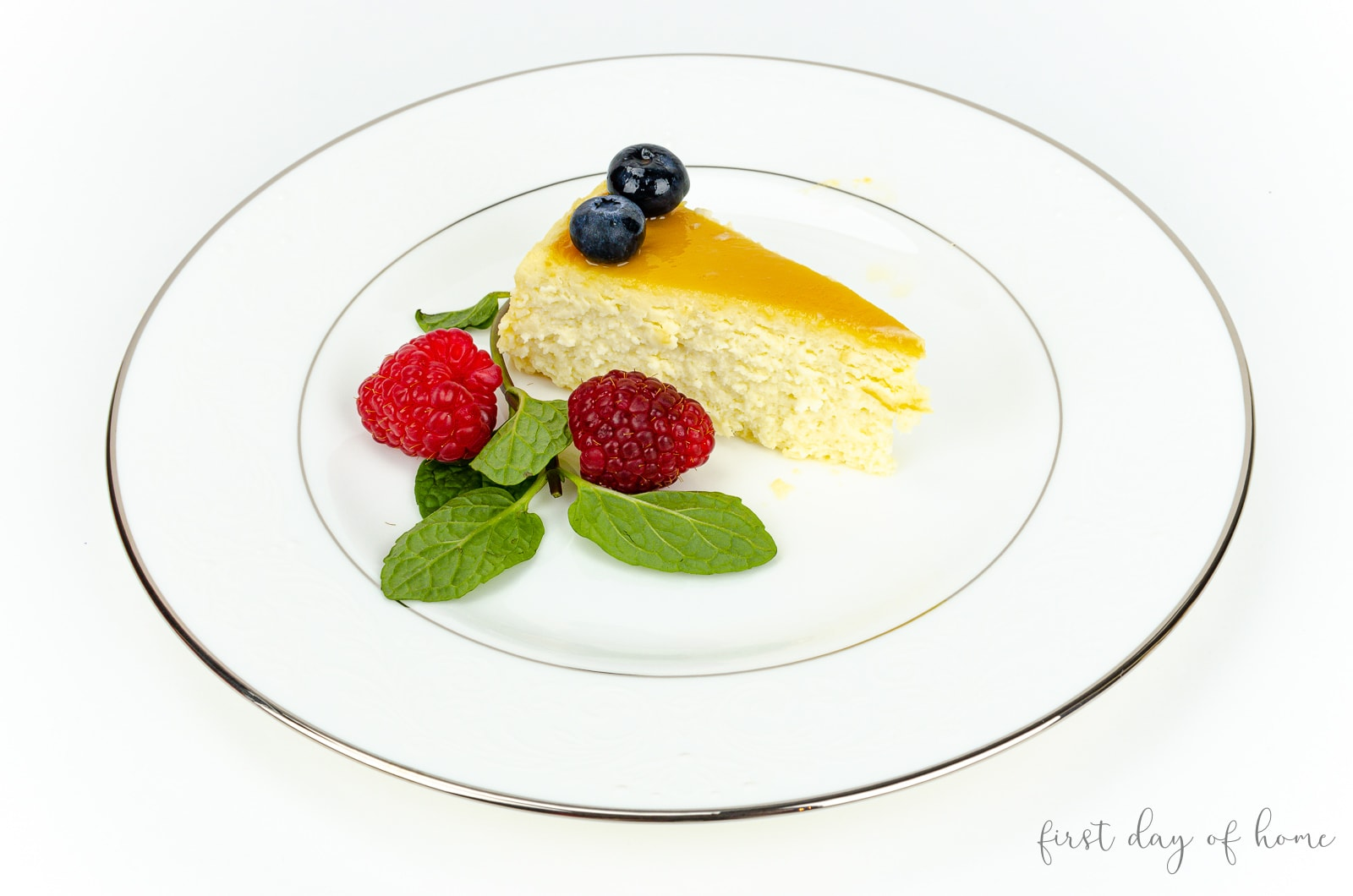 Flan de queso slice with mint leaves, raspberries and blueberries