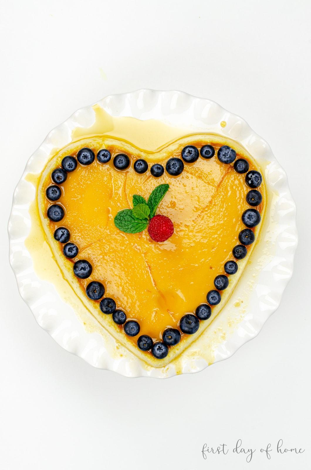 Heart shaped cheesecake flan recipe with blueberries, raspberries and garnish