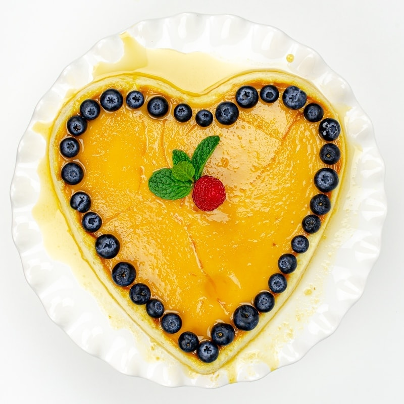 Heart shaped cheesecake - flan de queso - with raspberry, blueberries and mint garnish