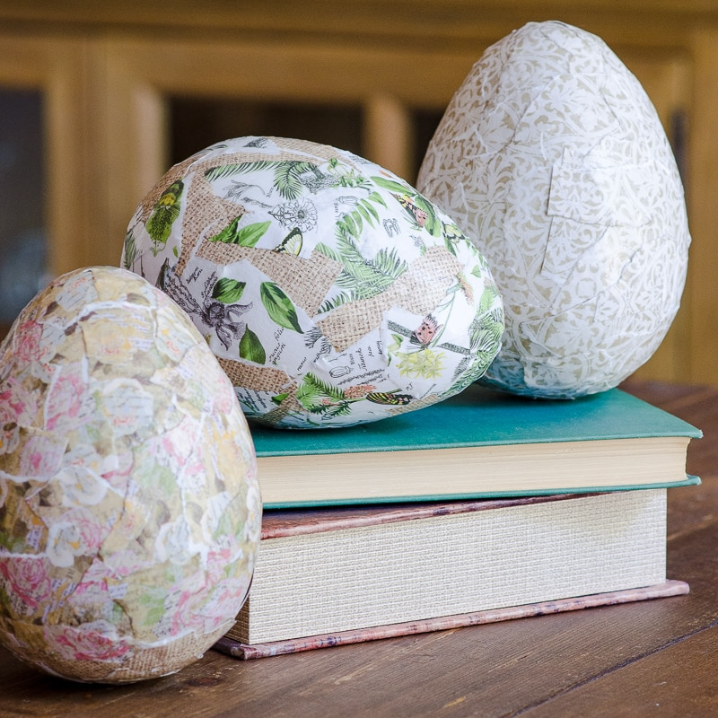Three decoupage Easter eggs sitting on books