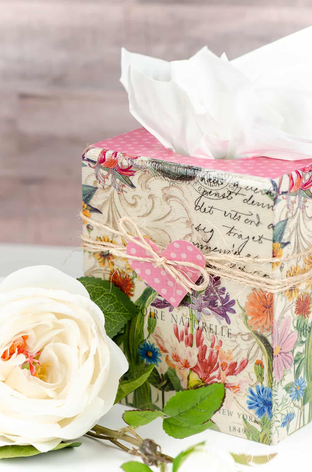 Wooden tissue box with decoupage napkins next to white rose