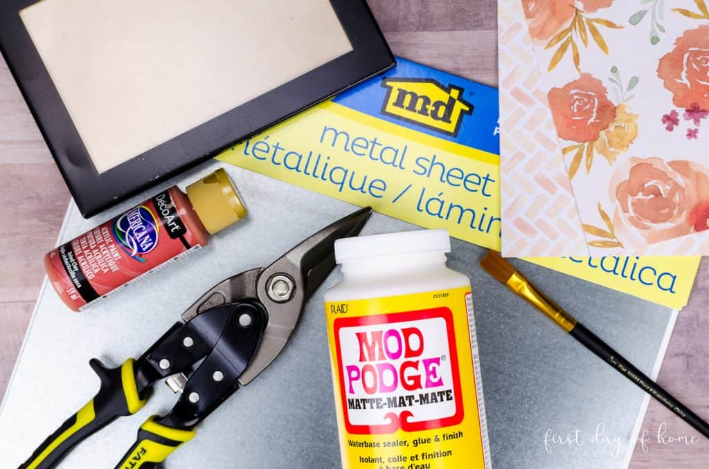 Supplies for upcycling a picture frame, including Mod Podge, clippers, metal sheet, frame, scrapbook paper and paint