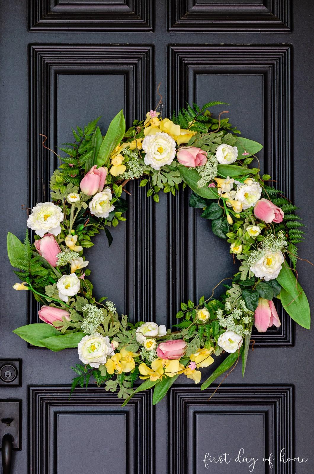 DIY spring wreath with faux florals on black front door
