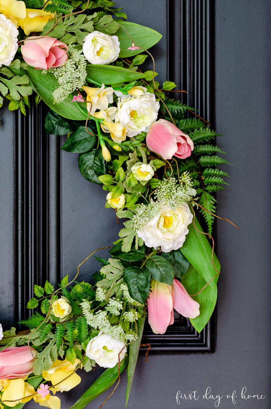 DIY spring wreath on front door with mix of tulips, yellow flowers and white ranunculus