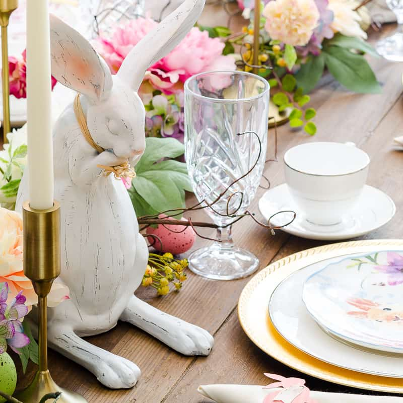 Easter table decor with spring garland, bunny statues and bunny place settings
