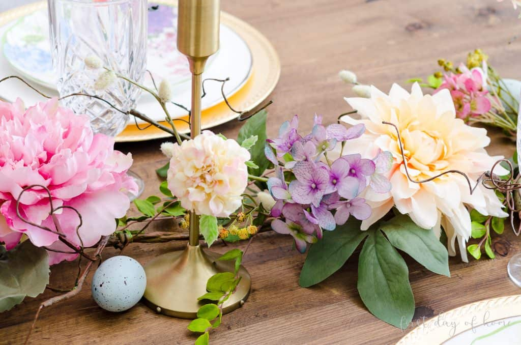 Faux floral spring garland with gold taper candle holders and Easter egg
