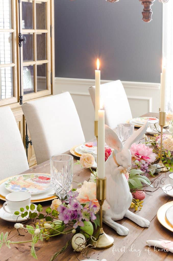 Easter table decorations with gold taper candle holders, floral garland and place settings