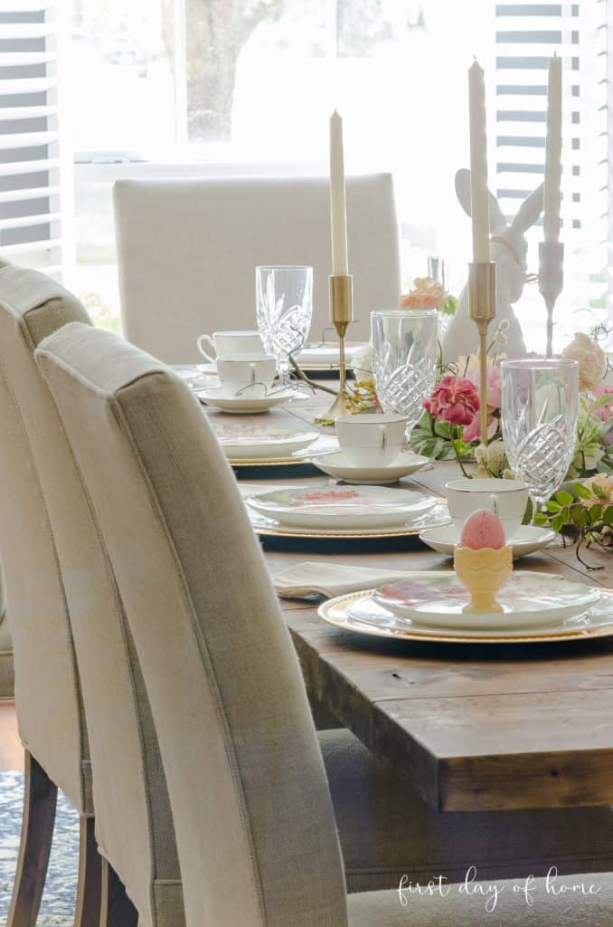 Easter table decorated with bunnies, egg cups, bunny plates and other festive decorations