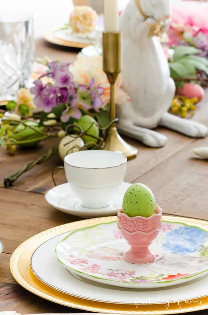 Green egg sitting in egg cup on place setting with gold charger and bunny plate
