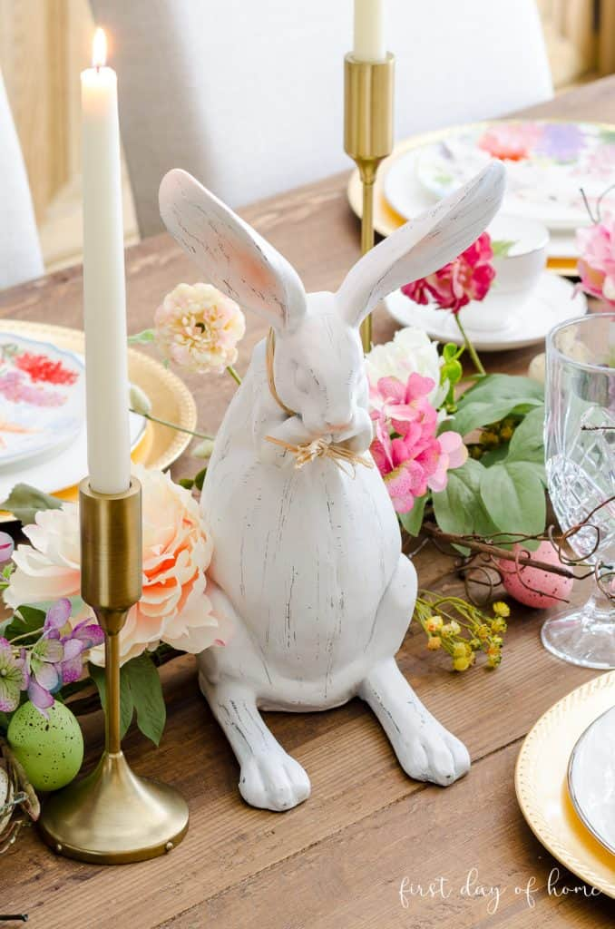 Easter bunny figurine with taper candles and floral garland on wooden table