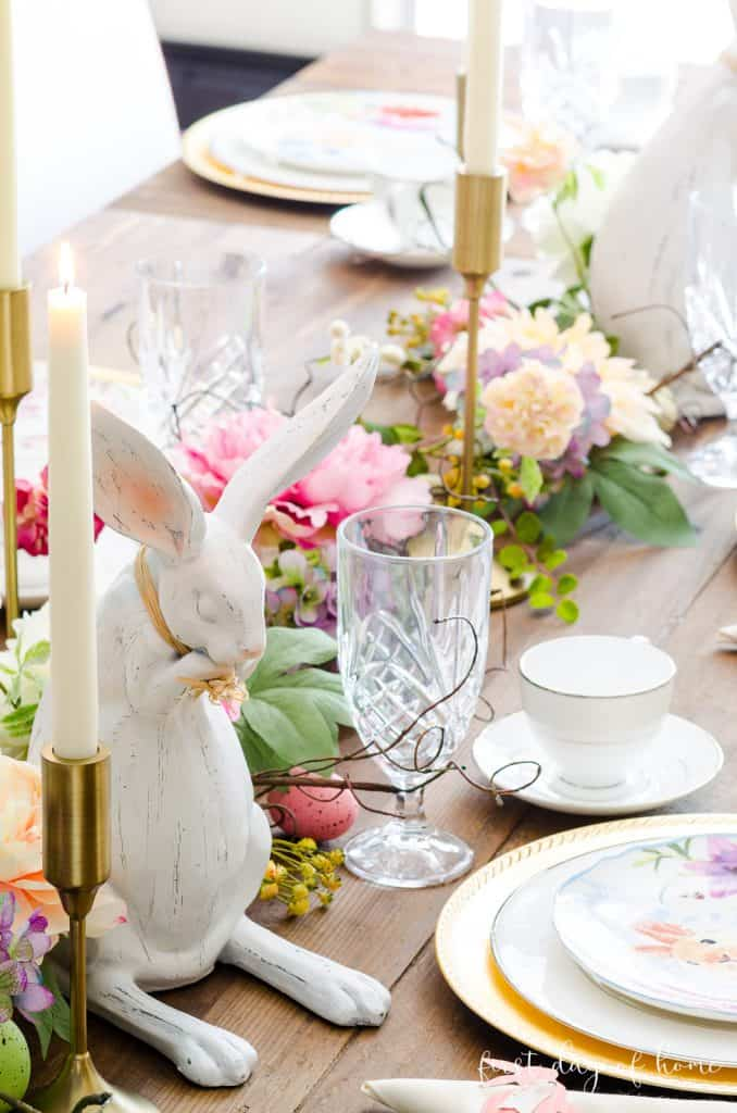 Easter table decorating ideas with place settings, bunny figurines, floral garland a taper candles