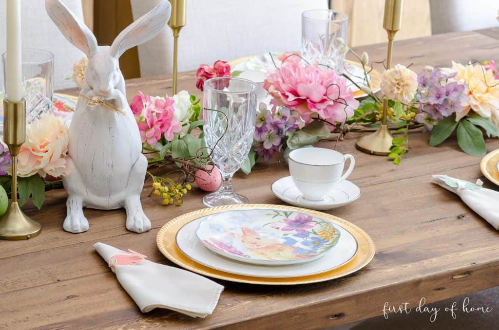 Easter place setting with gold chargers, bunny plate, bunny napkin rings and faux floral garland