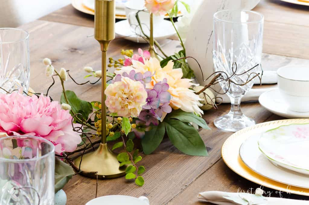 Faux floral garland on rustic farmhouse table with taper candle holders