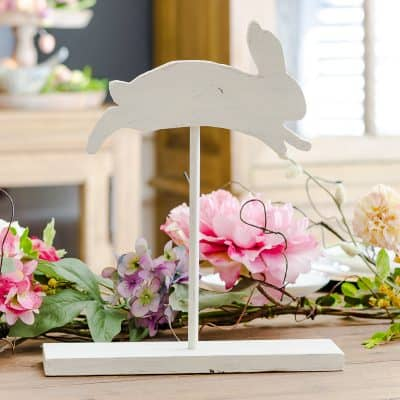 Wooden bunny on stand in front of floral garland Easter table