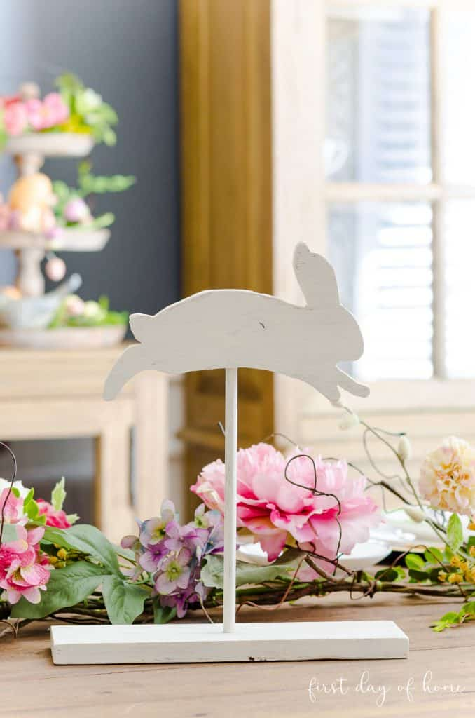 Wooden bunny on stand sitting on spring tablescape with floral garland